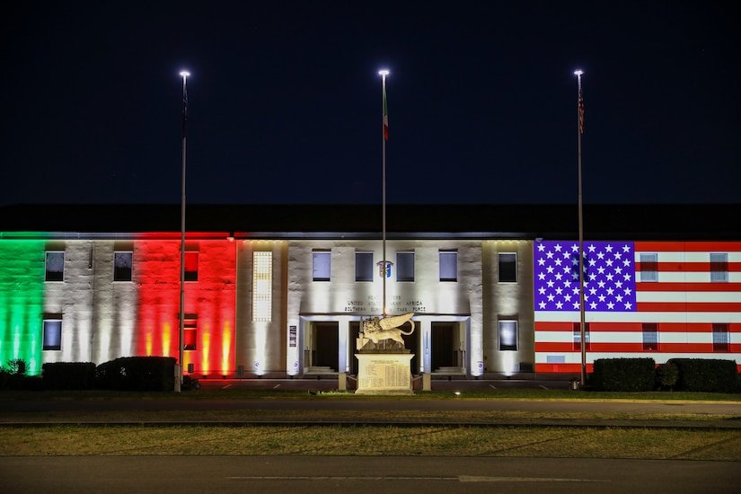 A building illuminated with the Italian and American flags.