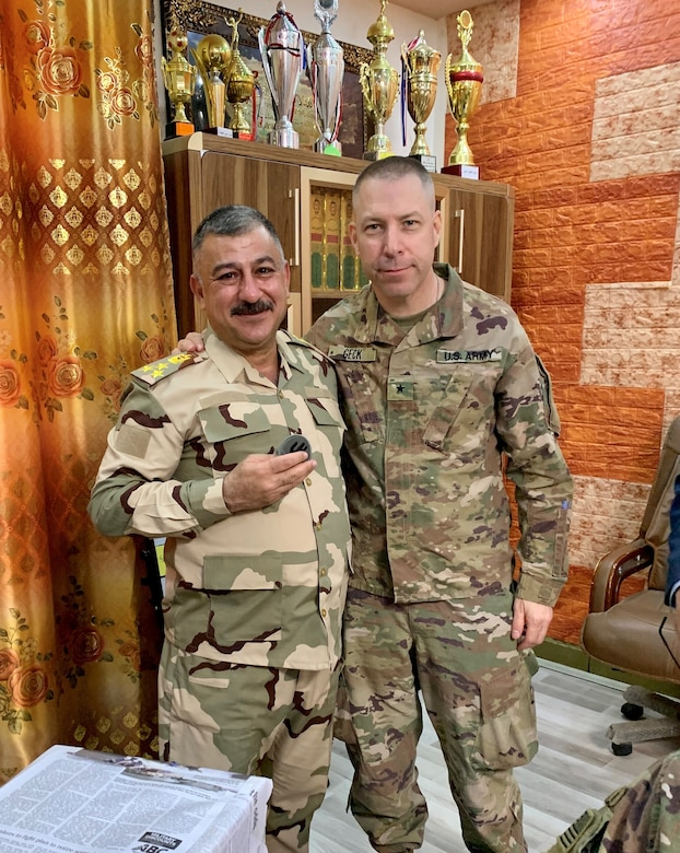 U.S. Army Brig. Gen. Howard Geck, commanding general, 103rd Expeditionary Sustainment Command, presented the 103rd unit patch to Iraqi Army Brig. Gen. Mae'n, commander of the Iraqi Army Western Track Repair Facility, at Camp Taji, Iraq, Feb. 24, 2020.  (U.S. Army National Guard photo by Capt. Richard Wharton)