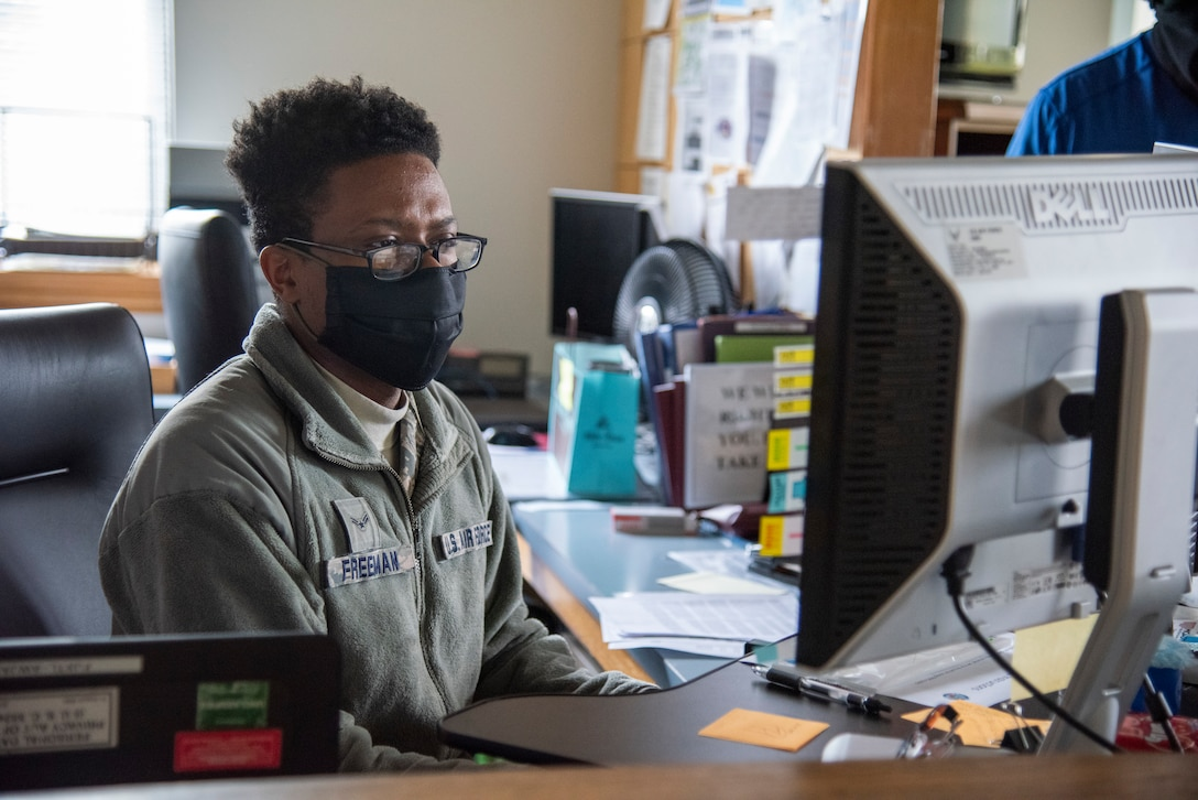 Airman 1st Class Malik Freeman, 436th Airlift Wing Legal Office paralegal, reviews information on a computer May 1, 2020, at Dover Air Force Base, Delaware. Freeman wears a mask in accordance with the Department of Defense instruction to reduce the spread of COVID-19. (U.S. Air Force photo by Airman 1st Class Jonathan Harding)