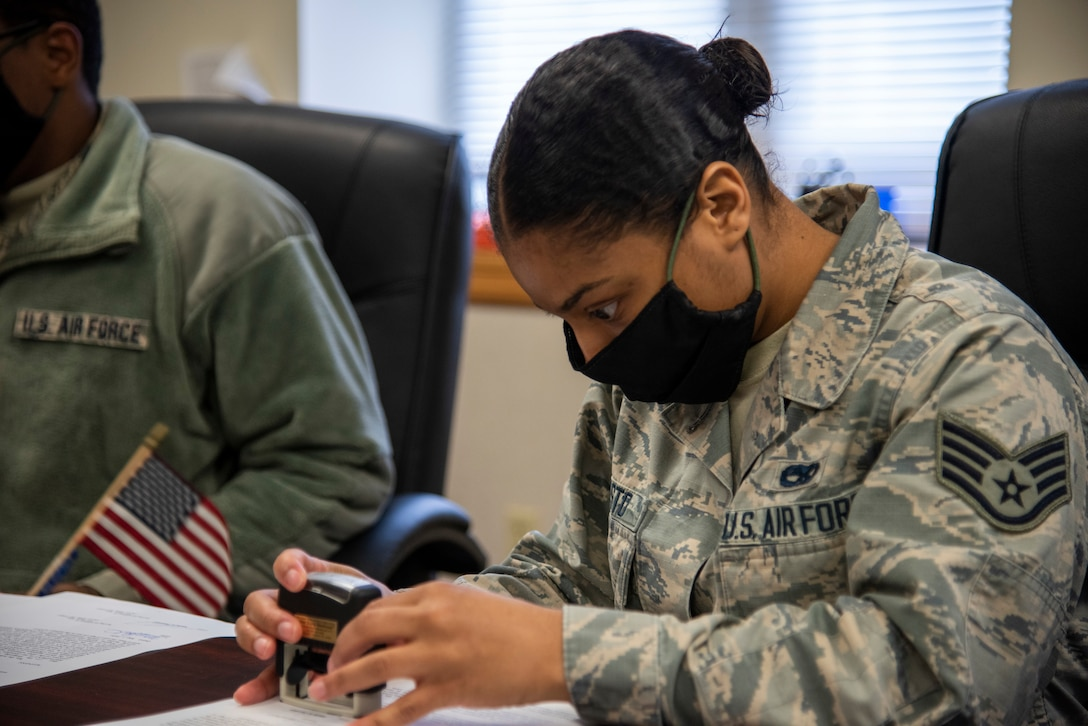 Staff Sgt. Tanea Resto, 436th Airlift Wing Legal Office NCOIC of military justice, stamps a document during an appointment May 1, 2020, at Dover Air Force Base, Delaware. Many legal office functions have shifted to teleworking; however, some appointments require in-person signatures. (U.S. Air Force photo by Airman 1st Class Jonathan Harding)