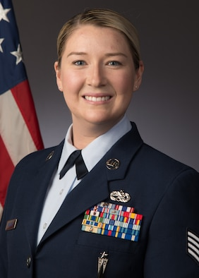 A studio photograph of a female Airman in her blues uniform