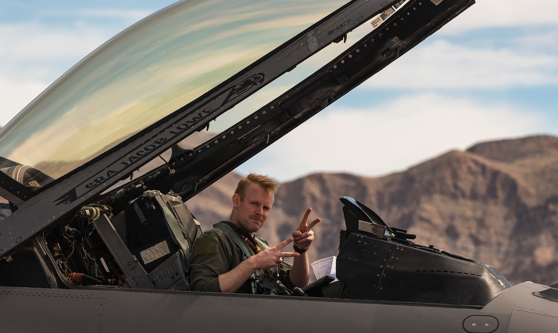 A picuture of a pilot sitting in the cockpit of a F-16.