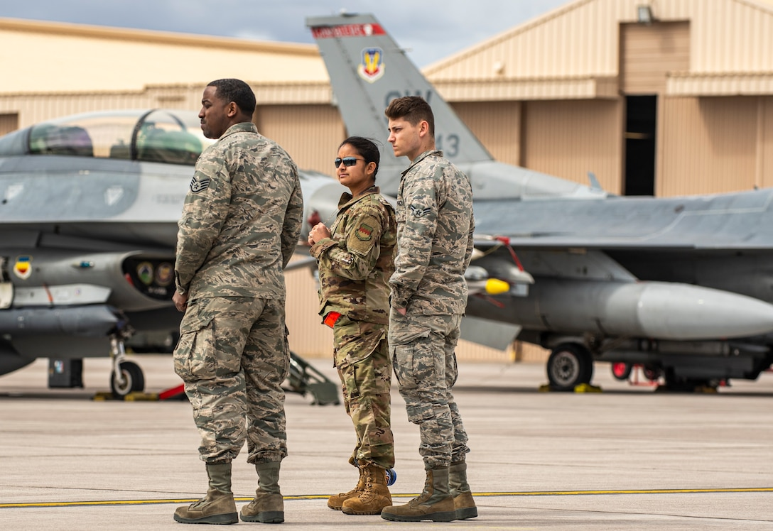 A group of Airmen stand on the flightline looking off in the distance.