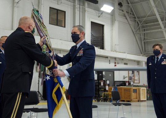 Col. William J. McCrink III, 174th Attack Wing Commander, receives the wing's colors from Maj. Gen. Ray Shields, New York State Adjutant General, signifying the transfer of command, during a Change of Command ceremony held at Hancock Field Air National Guard Base, May 3. (U.S. Air National Guard photo by Staff Sgt. Duane Morgan)