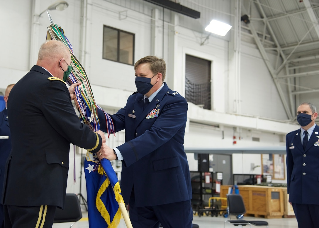 Col. Michael Smith, 174th Attack Wing commander, hands the wing's colors over to Maj. Gen. Ray Shields, New York State Adjutant General, signifying the transfer of command, during a Change of Command ceremony held at Hancock Field Air National Guard Base, May 3. (U.S. Air National Guard photo by Staff Sgt. Duane Morgan)