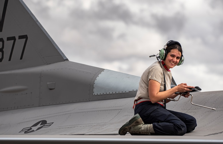 A picture of an Airman on top of a F-16.