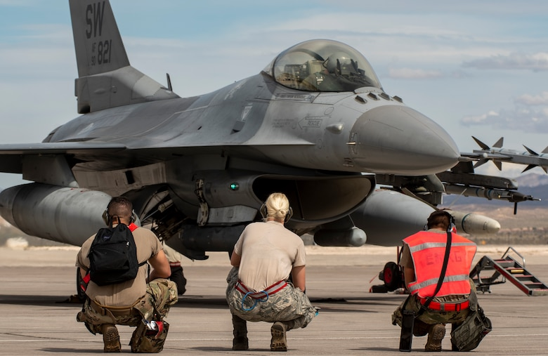 A picture of a group of Airmen sitting in front of a F-16.