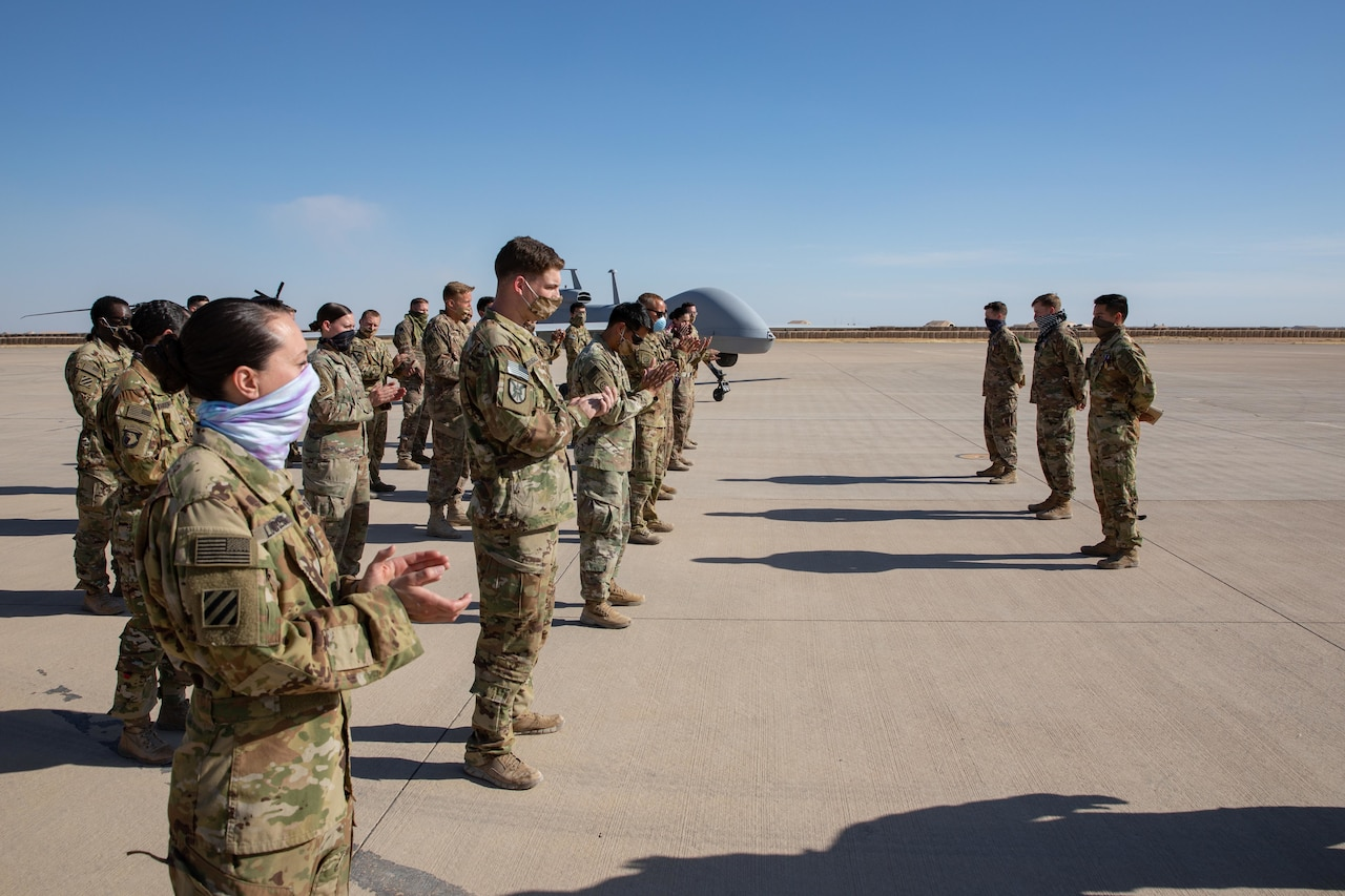 Soldiers wearing face masks practice social distancing in formation on a desert flight line.