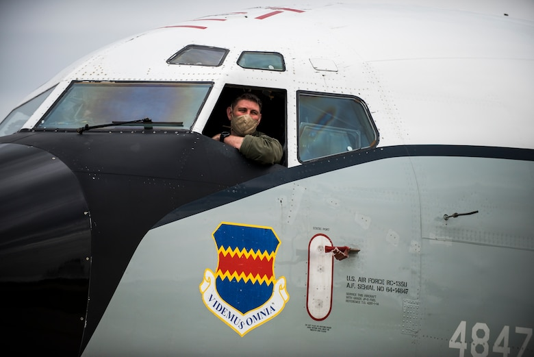 Pilot leans out window of aircraft.