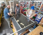 Jared David (left), Tracy Atkins (center) and Harlen Caldwell (right) assemble clean barrier made from vinyl in the Moonshine Lab at Puget Sound Naval Shipyard & Intermediate Maintenance Facility May 4. This team is part of a cadre of innovators taking on the challenge of designing and building protective barriers for customer facing interactions within the shipyard.