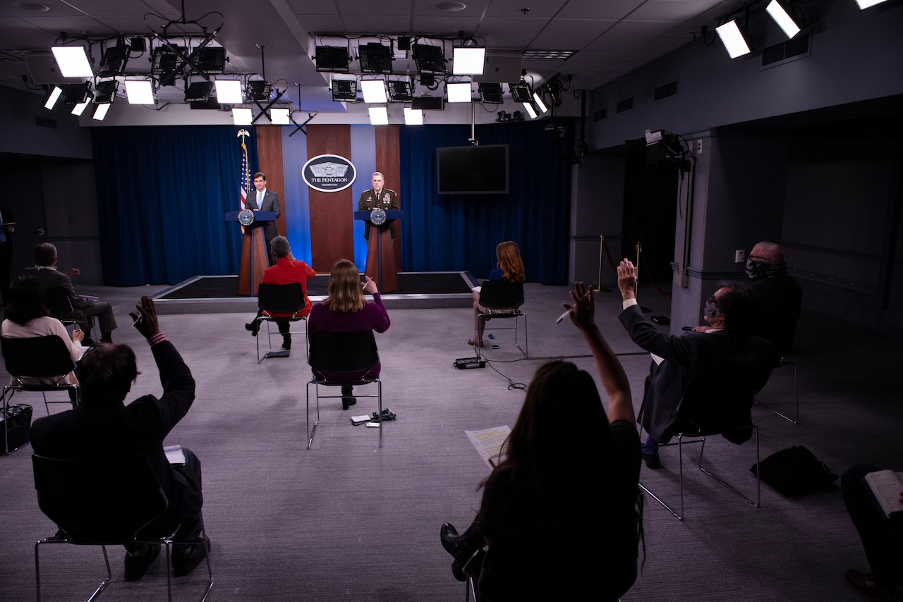 Socially distanced reporters raise their hands at a news conference.