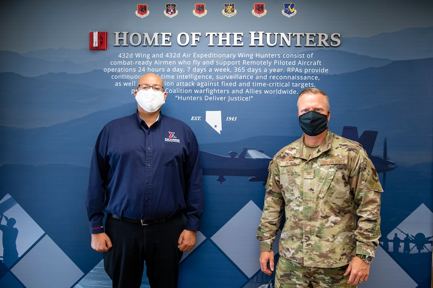 Col. Brian Snyder, 432nd Mission Support Group commander, and Matthew Beatty, Nellis/Creech Air Force Base Exchange general manager, pose for a photo inside a blue mural.