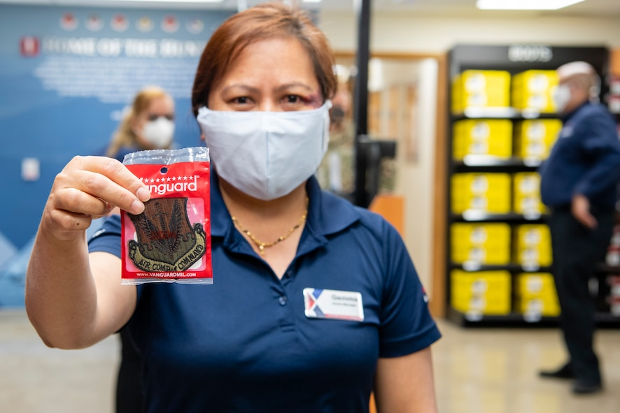 Gemma Prasad, Creech Military Clothing Sales manager, holds out an Air Combat Command patch during the soft opening of the military clothing store.