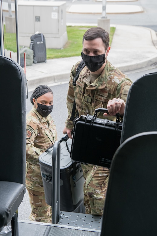 A C-17 Globemaster III aircrew with the 3rd Airlift Squadron enters a transport bus using the rear emergency door May 1, 2020, at Dover Air Force Base, Delaware. Entering from the rear of the bus and installing a plexiglass partition between the driver's seat and the passenger section help mitigate the potential spread of COVID-19 while transporting aircrews to and from the flight line. (U.S. Air Force photo by Mauricio Campino)