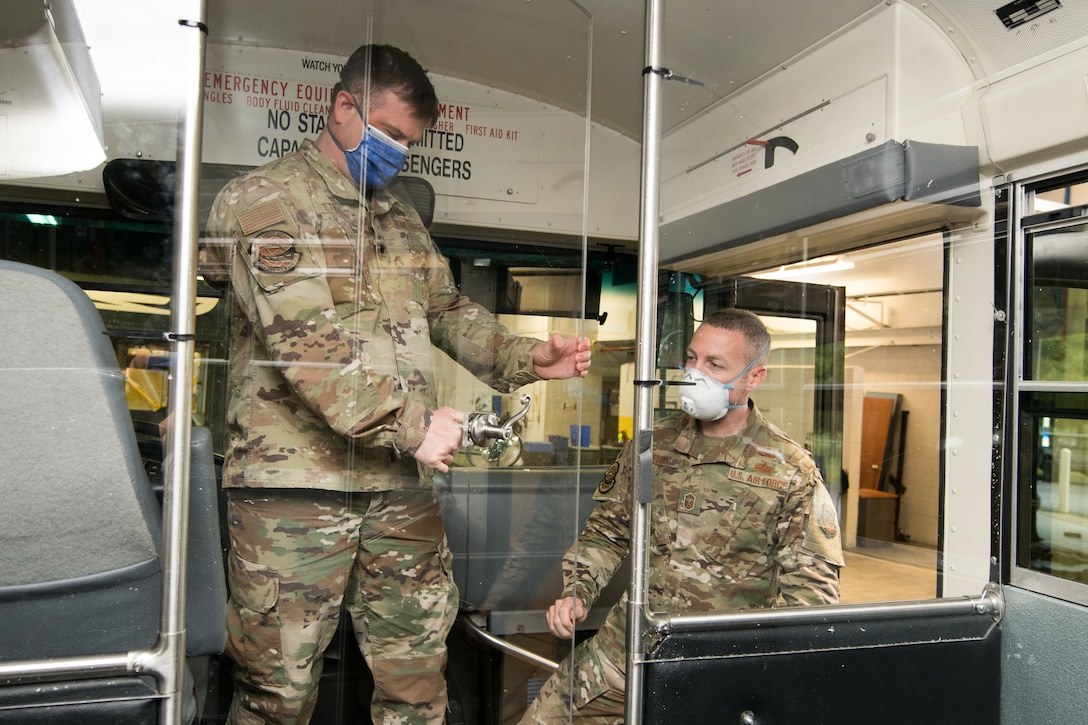 Lt. Col. Kevin Etherton, 436th Logistics Readiness Squadron commander and Senior Master Sgt. Troy Dubois, 436th Logistics Readiness Squadron Deployment and Distribution Flight superintendent, inspect the finished modifications to a transport bus April 27, 2020, at Dover Air Force Base, Delaware. Airmen of the 436th LRS installed a plexiglass partition between the driver's seat and the passenger section on several buses to help mitigate the potential spread of COVID-19 while transporting aircrews to and from the flight line. (U.S. Air Force photo by Mauricio Campino)