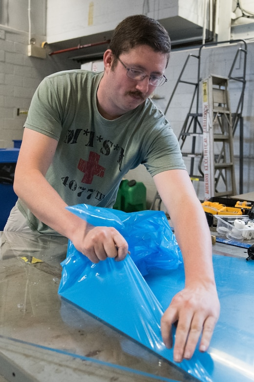 Staff Sgt. Cory Nelson, 436th Logistics Readiness Squadron Ground Transportation Support noncommissioned officer in charge, removes the protective cover from a sheet of plexiglass April 27, 2020, at Dover Air Force Base, Delaware. Despite being off duty, Nelson meticulously measured and cut each piece to ensure a proper fit. The installation of plexiglass barriers on transport buses further mitigates the spread of COVID-19, protecting the health and safety of 436th LRS Airmen and aircrew. (U.S. Air Force photo by Mauricio Campino)