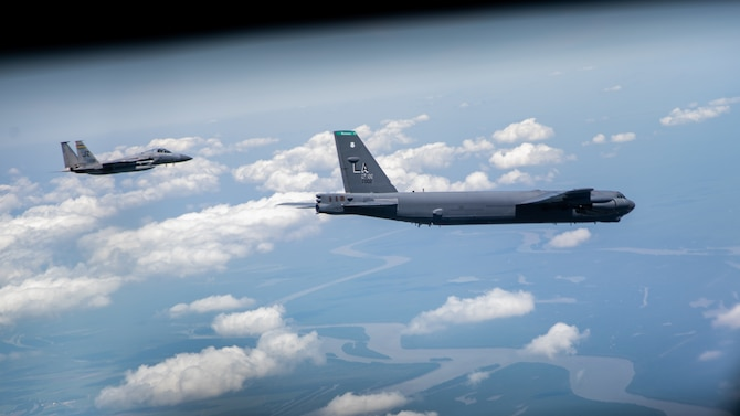 A B-52H Stratofortress and an F-15 Strike Eagle fly over South Louisiana, May 1, 2020.