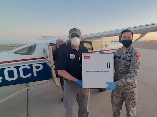 New Mexico Civil Air Patrol Maj. Gregory Griffith, left, and Flight Officer Casey Neal carry a package of COVID-19 test kits from the CAP aircraft to a vehicle for transport from Albuquerque International Airport to a laboratory for processing.
