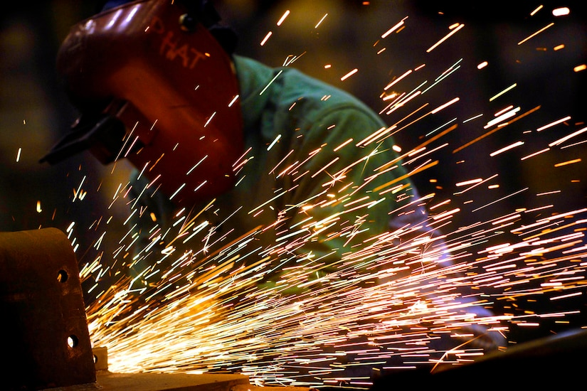Sparks fly off of metalwork. A worker wears a protective hood.