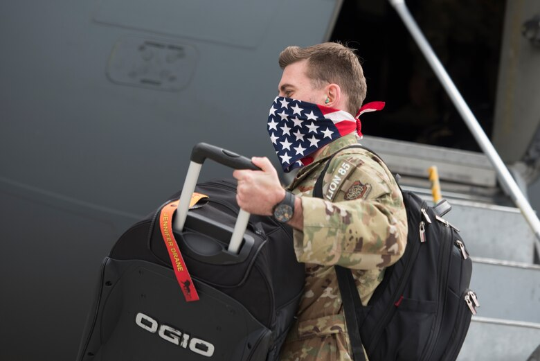 A photo of an Airman bringing his luggage off of a plane.