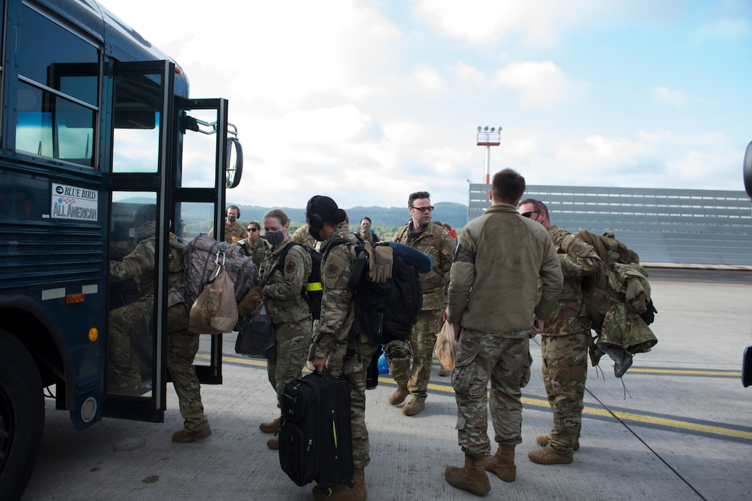 A photo of Airmen stepping onto a bus.