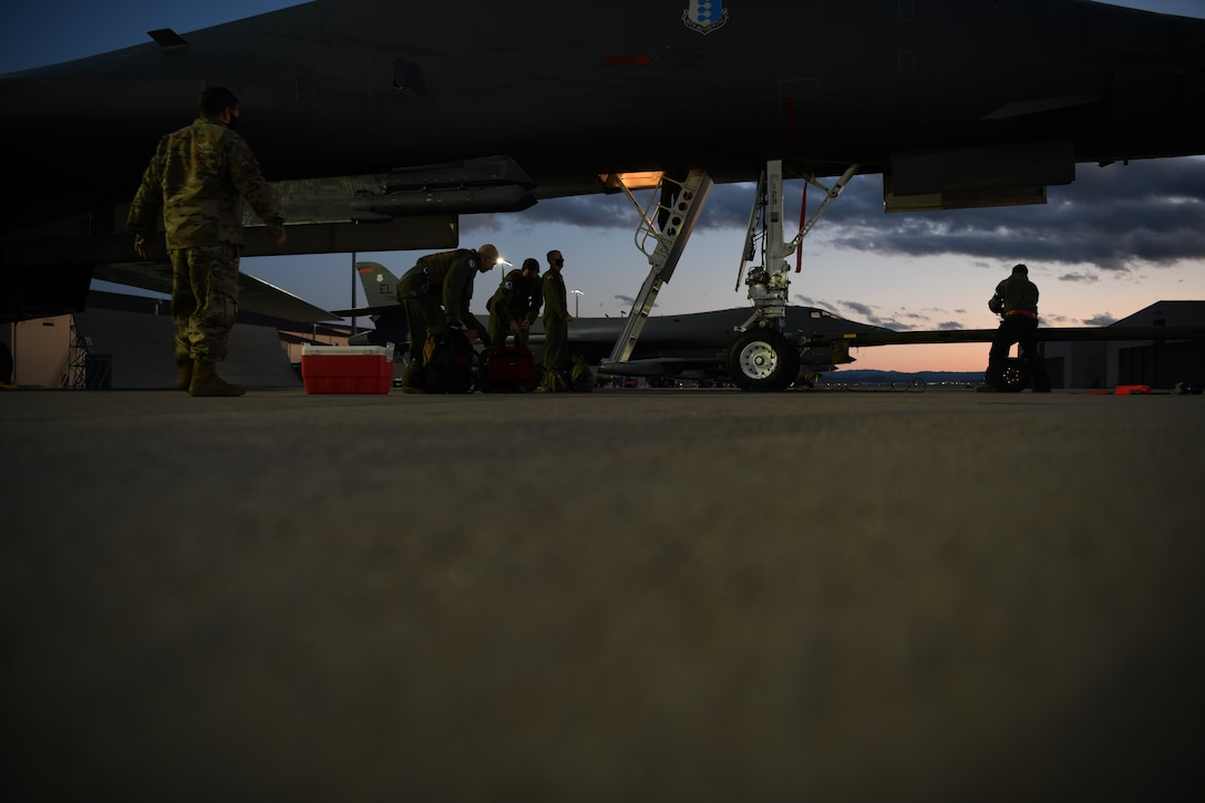 Wing leaders assist aviators assigned to the 34th Bomb Squadron unload their gear after successfully completing a more than 25-hour non-stop deployment from Ellsworth Air Force Base, S.D., May 5, 2020. During the Bomber Task Force mission to the U.S. European Command area of responsibility, B-1B Lancers integrated with NATO and allied partners for operations and activities. (U.S. Air Force photo by Senior Airman Nicolas Z. Erwin)