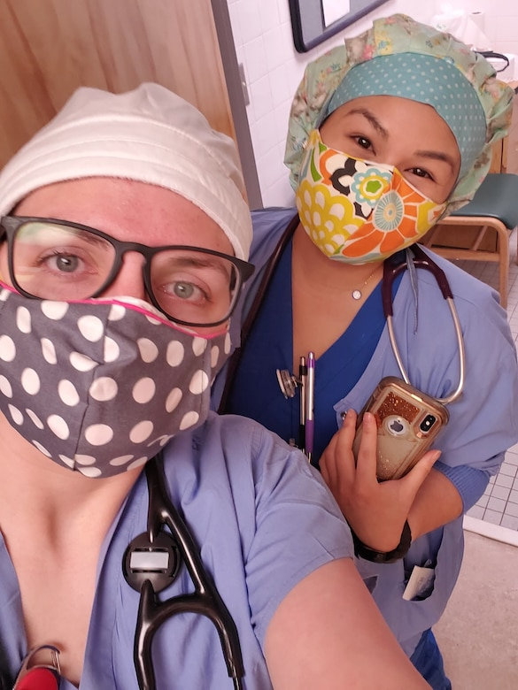 two white females in blue scrubs wearing masks, head coverings and stethoscopes.
