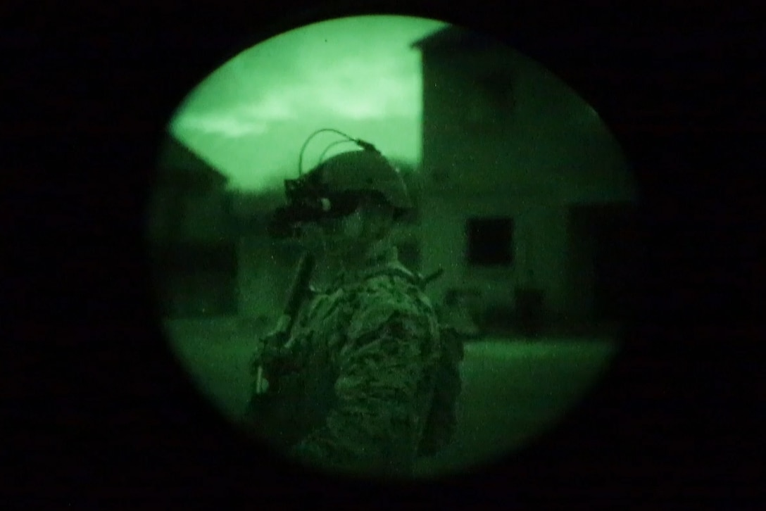 Through a camera lens, a Marine can be seen wearing night vision goggles.