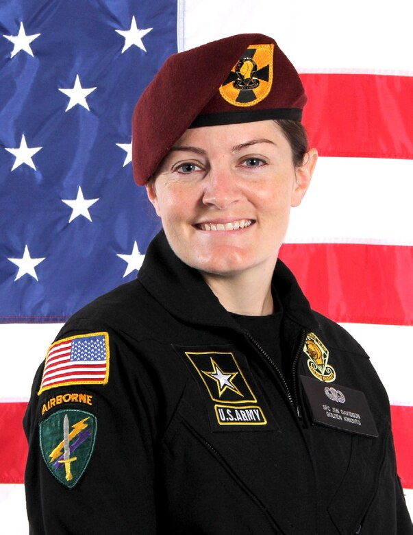 White female in black uniform with patches and maroon beret with gold and black flash stands in front of an American flag.