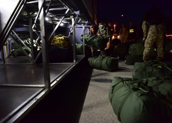 Soldiers with the 344th Military Intelligence Battalion load their bags onto a bus on Goodfellow Air Force Base, Texas, May 5, 2020. The Soldiers were the first class of U.S. Army intelligence graduates to move to their operational units during the COVID-19 restrictions. (U.S. Air Force photo by Staff Sgt. Chad Warren)