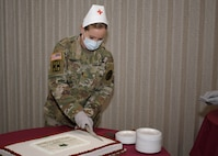 Maj. Betty Moore, the chief of ambulatory nursing, U.S. Army Medical Department Activity (MEDDAC), Fort Drum, N.Y., begins cutting a cake during the National Nurses Week kick-off celebration at the Guthrie Ambulatory Healthcare Clinic on Fort Drum, May 6.