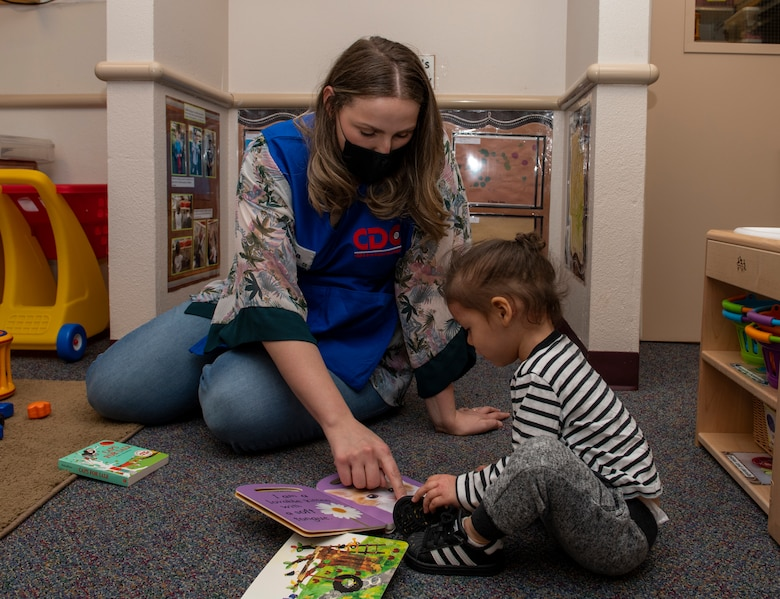 Emilia Williams, 60th Force Support Squadron child and youth program technician, helps a child read a book May 1, 2020, inside Child Development Center 3 at Travis Air Force Base, California. Travis AFB has three childcare centers that have cared for children during the coronavirus pandemic. (U.S. Air Force photo by Tech. Sgt. James Hodgman)