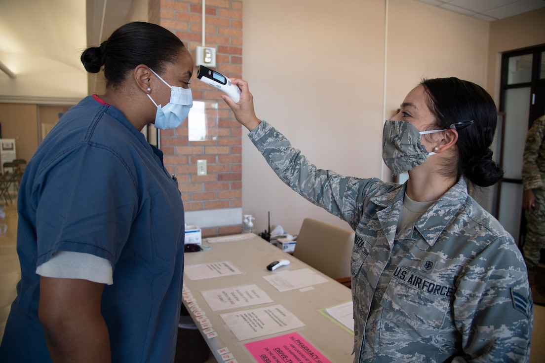 Senior Airman Maria Mendoza, right, a physical therapy technicial in the 82nd Operational Medical Readiness Squadron, checks Capt. Denean Zozo's temperature at the 82nd Medical Group single-point-of-entry screenling location at Sheppard Air Force Base, Texas, May 6, 2020. Staff, patients and other guests to the 82nd MDG are screened at the pharmacy entrance before going any farther into the facility. People who exhibit symptoms of COVID-19 – temperature of 100.4 degrees or higher, cough, sore throat and shortness of breath – are sent to the triage area behind the screening desk for more evaluation. (U.S. Air Force photo by Senior Airman Pedro Tenorio)