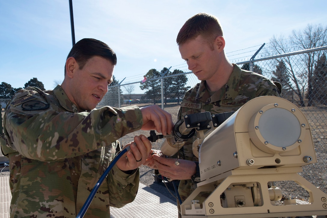 Two airmen work on an antenna.