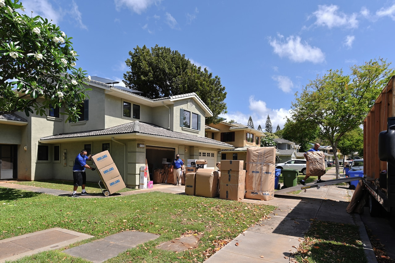 Workers move boxes out of a home. Many other boxes sit on a driveway.
