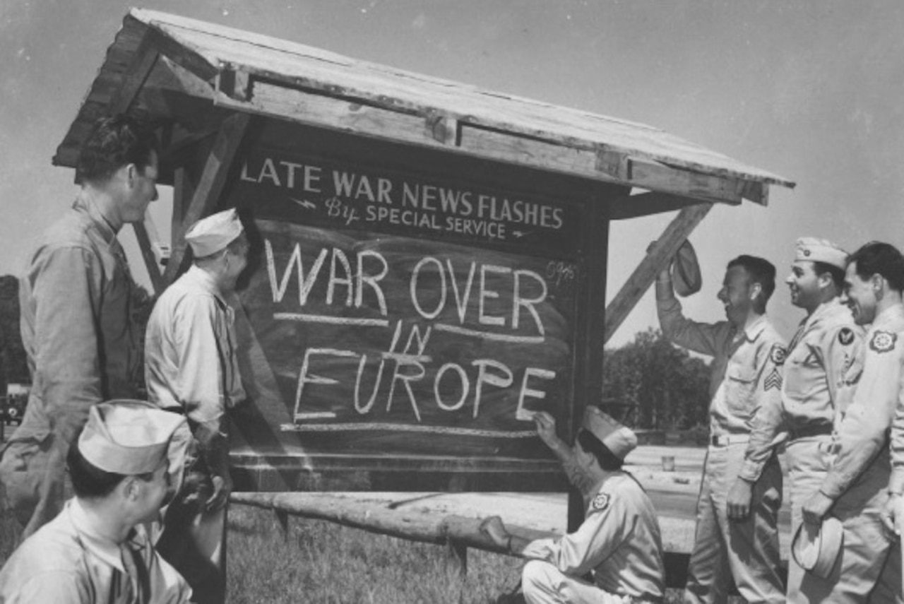 "Service members stand around a sign reading ""War Over in Europe"""