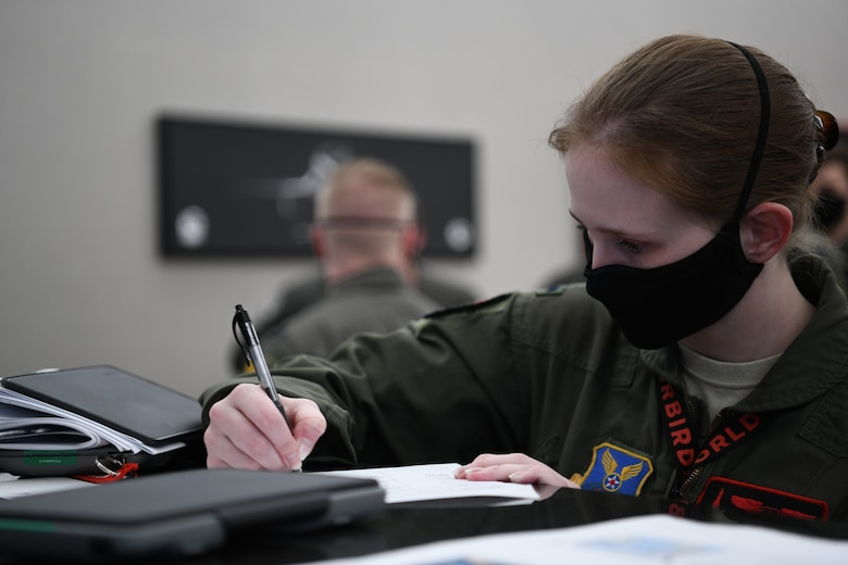 A 34th Bomb Squadron aviator writes mission information for a non-stop deployment from Ellsworth Air Force Base, S.D., May 4, 2020. Bomber deployments and operations enhance the readiness and training necessary to respond to any contingency or challenge across the globe. (U.S. Air Force photo by Airman Quentin Marx)