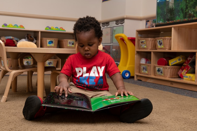 A child reads a book May 1, 2020, inside Child Development Center 3 at Travis Air Force Base, California. The center is one of three childcare centers at Travis AFB that provide care for children from six weeks to 5-years-old. (U.S. Air Force photo by Tech. Sgt. James Hodgman)