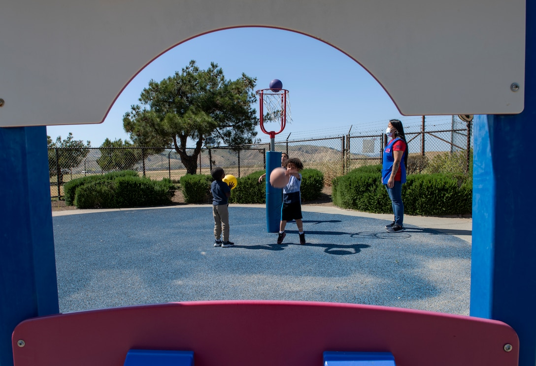 Cheryl Jose, right, 60th Force Support Squadron child and development program technician, supervises children May 1, 2020, as they play outside Child Development Center 3 at Travis Air Force Base, California. Travis AFB has three childcare centers that have cared for military children during the coronavirus pandemic. (U.S. Air Force photo by Tech. Sgt. James Hodgman)