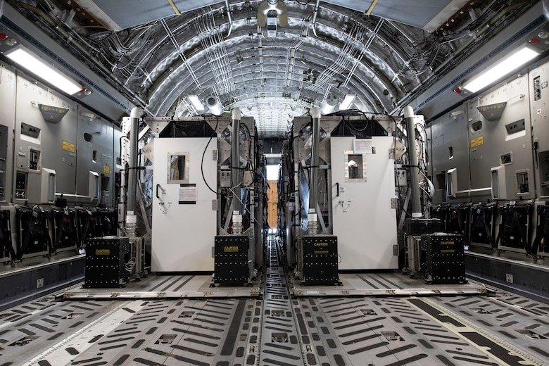 Two Transport Isolation System capsules are placed in the cargo bay of a C-17 Globemaster III April 28, 2020, at Travis Air Force Base, California. TIS capsules, which were initially engineered in response to the Ebola virus in 2014, allow the transport of individuals with highly contagious diseases without infecting any other passengers or aircrew on the aircraft. (U.S. Air Force photo by Senior Airman Christian Conrad)