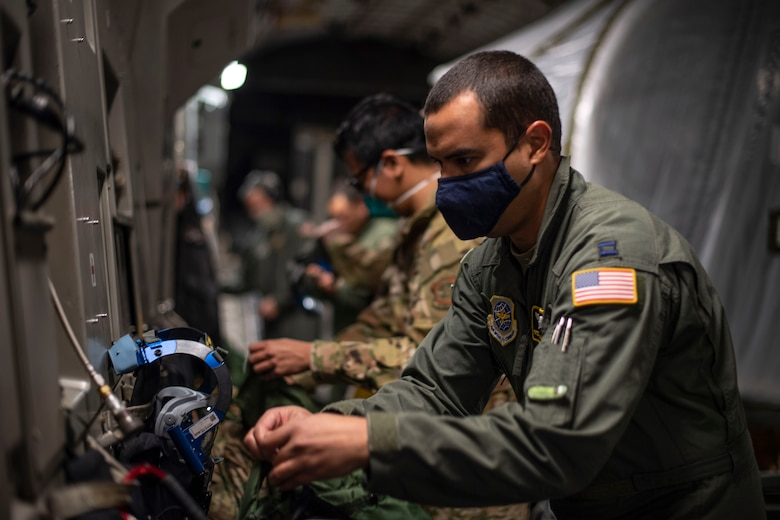 U.S. Air Force Capt. Freddy Roman-Otero, 43rd Aeromedical Evacuation Squadron flight nurse, checks his equipment as part of a pre-flight procedure April 27, 2020, at Travis Air Force Base, California. Roman-Otero is one of two 43rd AES representatives called to perform training on the Transport Isolation System capsule. This training coincided with the 21st Airlift Squadron's transfer of four TIS capsules from Joint Base Charleston, South Carolina, to Travis AFB in an effort to bolster the U.S. Air Force's AE capabilities. . (U.S. Air Force photo by Senior Airman Christian Conrad)