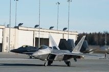 A U.S. Air Force F-22 Raptor taxis onto the runway prior to an elephant walk, May 5, 2020, at Joint Base Elmendorf-Richardson, Alaska. This event displayed the ability of the 3rd Wing, 176th Wing and the 477th Fighter Group to maintain constant readiness throughout COVID-19 by Total Force Integration between active-duty, Guard and Reserve units to continue defending the U.S. homeland and ensuring a free and open Indo-Pacific.