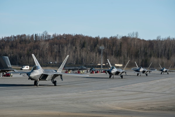 U.S. Air Force F-22 Raptors taxi onto the runway prior to an elephant walk, May 5, 2020, at Joint Base Elmendorf-Richardson, Alaska. This event displayed the ability of the 3rd Wing, 176th Wing and the 477th Fighter Group to maintain constant readiness throughout COVID-19 by Total Force Integration between active-duty, Guard and Reserve units to continue defending the U.S. homeland and ensuring a free and open Indo-Pacific.