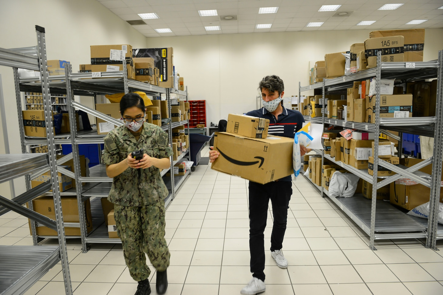 NAPLES, Italy (April 30, 2020) Francesco Ciccarelli, postal clerk (right), and Logistics Specialist Seaman Oralia Ortiz sort and organize incoming mail at the Naval Support Activity (NSA) Naples Support Site post office, attached to Naval Supply Systems Command Fleet Logistics Center (NAVSUP FLC) Sigonella, April 30, 2020. Commander, U.S. Naval Forces Europe-Africa/ U.S. 6th Fleet, headquartered in Naples, Italy, oversees joint and naval operations, often in concert with Allied, joint, and interagency partners, in order to advance U.S. national interests and security and stability in Europe and Africa. (U.S. Navy photo by Mass Communication Specialist Chief Justin Stumberg/Released)