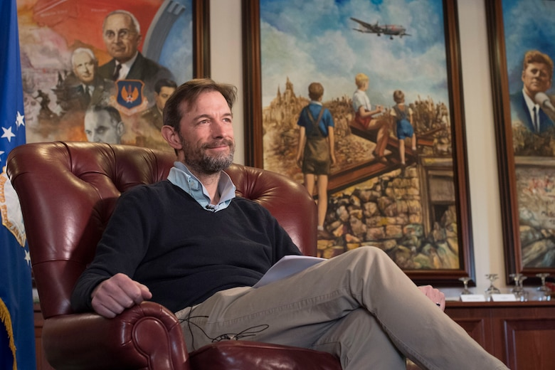 A man sits in a chair with historical paintings in the background.