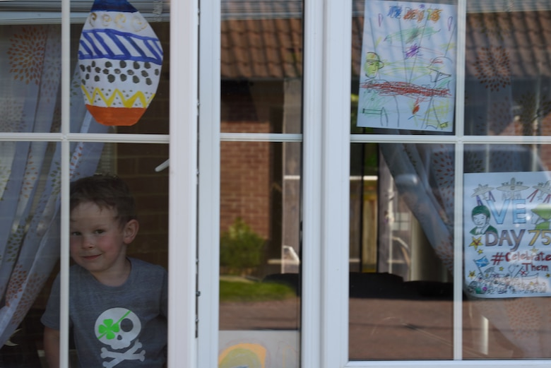 A child of a U.S. Air Force Airman displays Victory in Europe Day artwork in their window in Liberty Village at Royal Air Force Lakenheath, England, May 6, 2020. VE Day marked the end of World War II and serves as a day of reflection and to commemorate the bravery of the men and women who ushered in freedom across Europe. (U.S. Air Force photo by Airman 1st Smith Rhonda Smith)