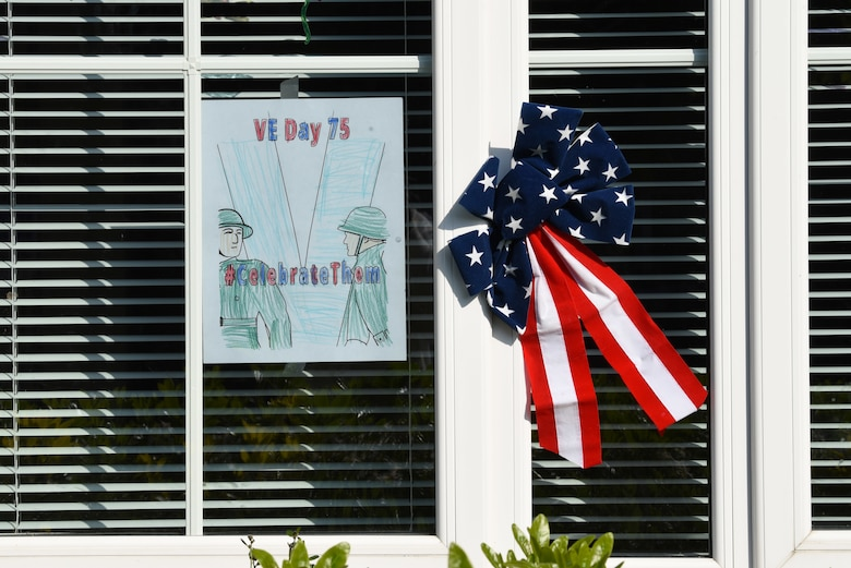 Victory in Europe Day artwork is displayed in a window in Liberty Village at Royal Air Force Lakenheath, England, May 6, 2020. On May 8, the U.K. will join the U.S. and allies around the world to mark the 75th anniversary of VE Day, with virtual programs to avoid the spread of COVID-19. (U.S. Air Force photo by Airman 1st Smith Rhonda Smith)