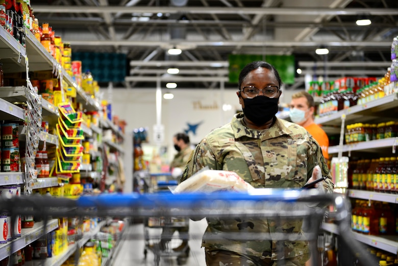 U.S. Air Force Tech. Sgt. Kahlia Rainer, 56th Helicopter Maintenance Unit instrument and flight control technician and grocery delivery volunteer, returns to her cart at the commissary on Aviano Air Base, Italy, April 18, 2020. Rainer delivered the groceries to a person unable to shop for themselves due to current COVID-19 restrictions. (U.S. Air Force photo by Tech. Sgt. Tory Cusimano)