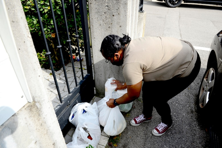 U.S. Air Force Tech. Sgt. Kahlia Rainer, volunteer, drops groceries off at the front gate of a home outside Aviano Air Base, Italy, April 18, 2020. The recipient was the spouse of an active duty member unable to shop with her children due to movement restrictions put in place by the Italian government to help battle COVID-19. (U.S. Air Force photo by Tech. Sgt. Tory Cusimano)