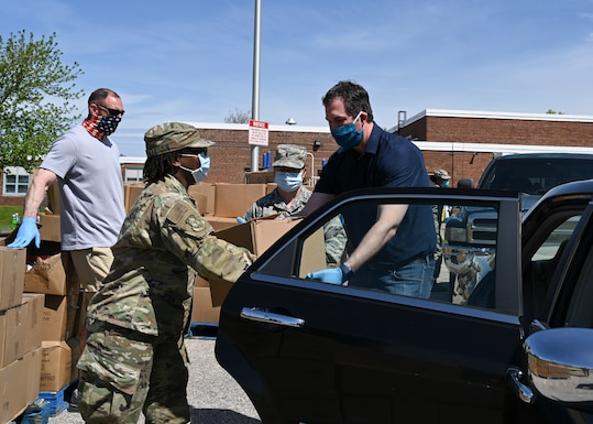 Airman 1st Class Clarissa Smith, a personnelist assigned to the 175th Force Support Squadron, Maryland Air National Guard, passes a box of groceries to Baltimore County Executive John Olszewski while supporting efforts by the Maryland Food Bank and Baltimore County Department of Parks and Recreation to distribute meals and groceries at the Mars Estates Police Athletic League center in Essex, Md., May 2, 2020. The mission ensures citizens have enough food supplies while schools and work places are closed. (U.S. Air National Guard photo by Tech. Sgt. Enjoli Saunders)